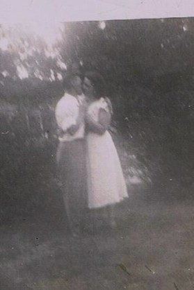 mom and dad hugging in the yard - cropped